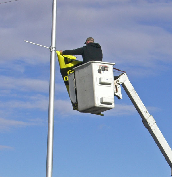 Worker installing pole display on light pole with bucket truck