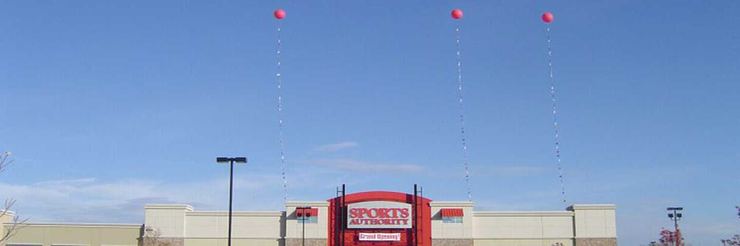 Three helium balloons in front of Sports Authority.